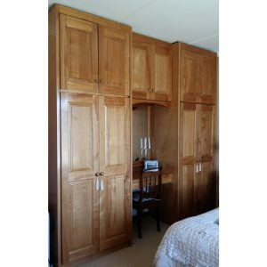 Built-in closet with dressing table and mirror in center in natural Okoume