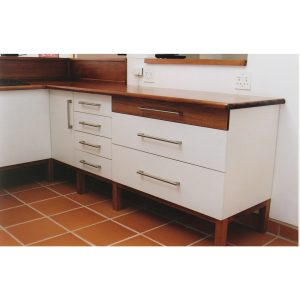 Kitchen cabinets with white lacquered surfaces, wood accents and stainless steel fittings